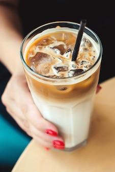 Mrożona kawa latte. kawa mrożona z mlekiem. kobieta trzyma szklaną filiżankę mrożonej kawy. czas na kawę w letni dzień. poranny nastrój. widok z góry