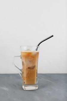 Mrożona kawa latte w przezroczystym szkle ze słomką wielokrotnego użytku.