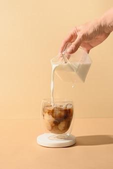 Mrożona kawa latte w szklance do kubka z wlewającym się mlekiem
