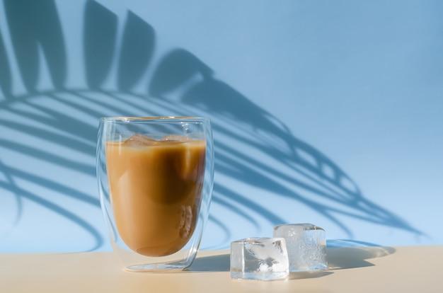 Mrożona kawa latte z mrożoną kostką na podłodze i cień z liści kokosa na brązowym i niebieskim tle. koncepcja letniego drinka.