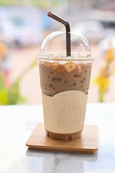 Mrożona kawa na wynos kubek plastikowego szkła na drewnianym stole w kawiarni ze ścieżką przycinającą na pustym papierze z etykietami na logo kawiarni makiety