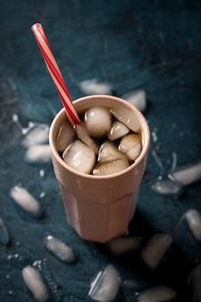 Mrożona kawa w szklance na ciemnoniebieskiej kamiennej powierzchni z kostkami lodu. koncepcja napój chłodzący, pragnienie, lato, cola z lodem, życie nocne, klub. leżał płasko, widok z góry