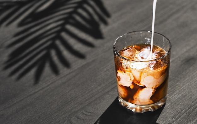 Mrożona kawa w szklance ze śmietaną i kostkami lodu na czarnym drewnianym stole zbliżenie selektywnej ostrości krem wlewa się do szklanki zimny letni napój z koncepcji gotowania kawy i mleka