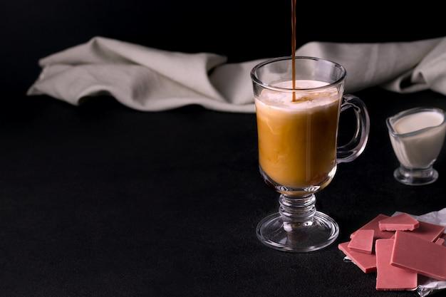 Mrożona kawa z karmelem i śmietanką obok ziaren kawy i różowa słodka czekolada