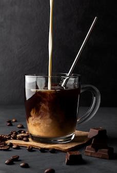Mrożona kawa ze śmietaną i metalową słomką na czarnej przestrzeni