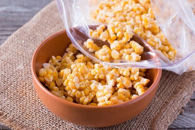 Mrożona kukurydza w misce na drewnianym stole
