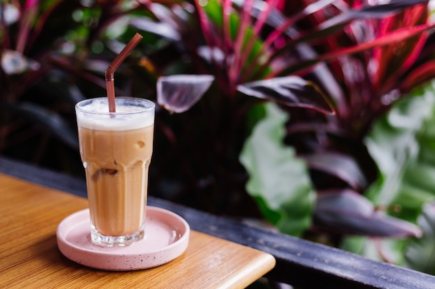 Mrożona latte w szkle na różowym stojaku na drewnianym stole w zielonych krzakach letniej kawiarni