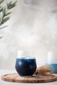 Mrożona niebieska herbata matcha w szklance na drewnianej desce