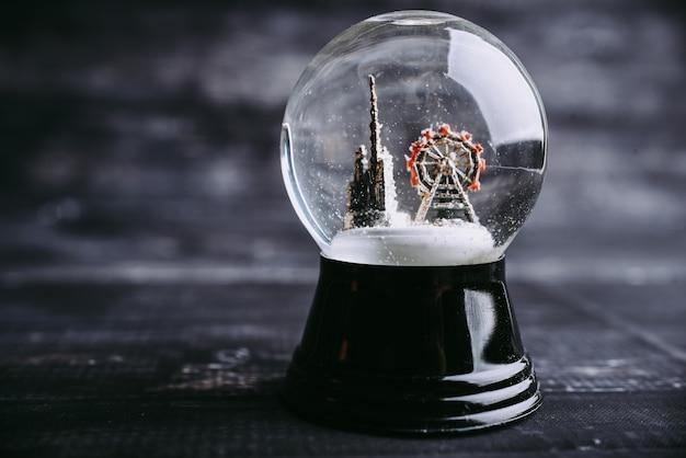 Mrożona śnieżna kula świąteczna magiczna kula z latającymi płatkami śniegu i kościołem i atrakcją.