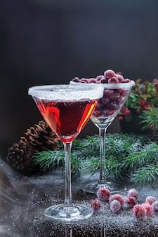 Mrożona żurawina w cukrze na ciemno w kieliszku koktajlowym na stole ozdobionym gałęziami i szyszkami choinkowymi.