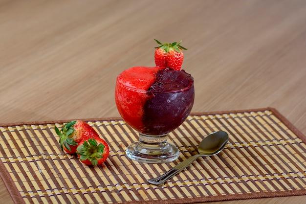 Mrożone acai i fresh strawberry cream bowl na rustykalnym drewnianym stole, pyszny deser