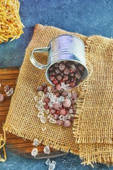 Mrożone jagody z lodem w blaszanym kubku na worku i siano na fioletowym tle