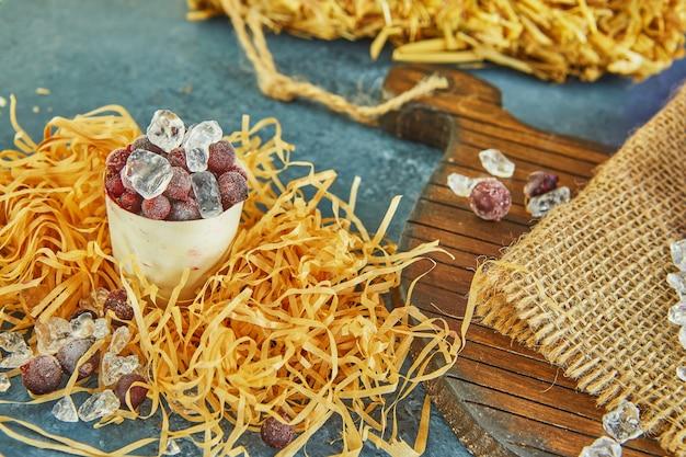 Mrożone jagody z lodem w rustykalnym talerzu, na workach i siano na fioletowym tle