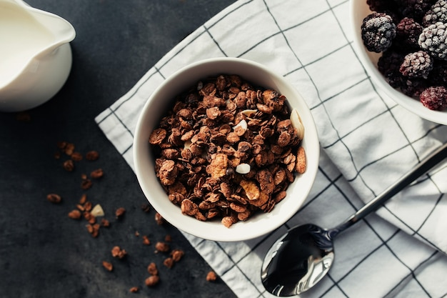 Mrożone jeżyny, granola, śmietana, ręcznik na stole. niewyraźne tło. wysokiej jakości zdjęcie