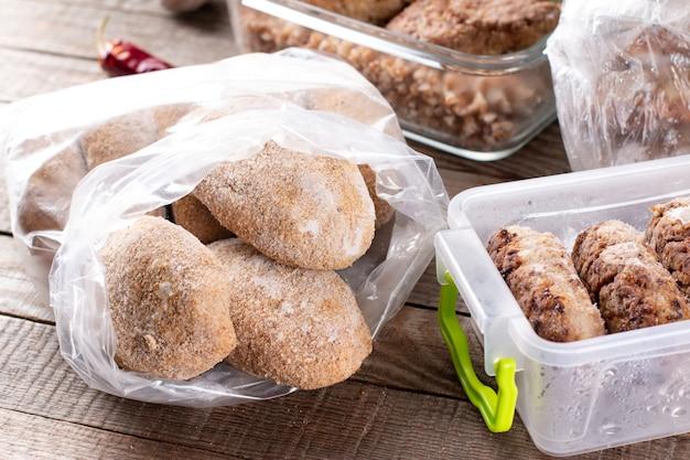 Mrożone kotlety lub klopsiki w plastikowej torbie na drewnianym stole, gotowe do spożycia