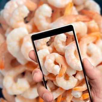Mrożone krewetki na ekranie smartfona.