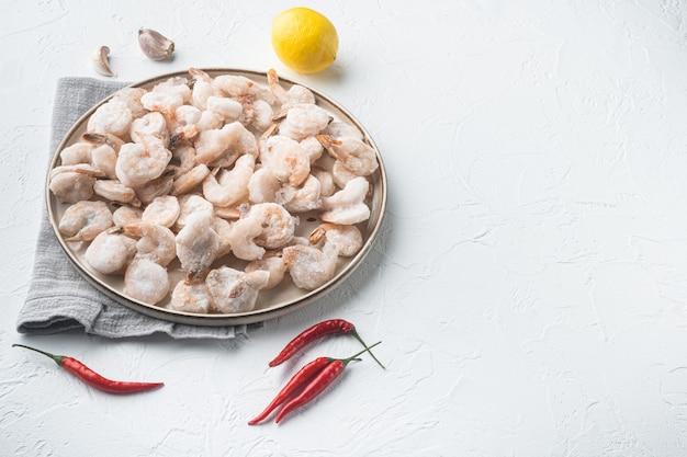 Mrożone obrane gotowane krewetki zestaw, na talerzu, na białym tle, z miejscem na kopię tekstu