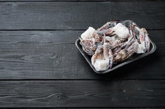 Mrożone surowe mięso kraba pływającego w kolorze niebieskim, na plastikowej tacy, na czarnym drewnianym stole