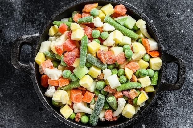 Mrożone surowe warzywa na patelni. wegetarianizm. czarne tło. widok z góry.