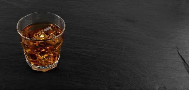 Mrożone szkło whisky na naturalne czarne tło kamień
