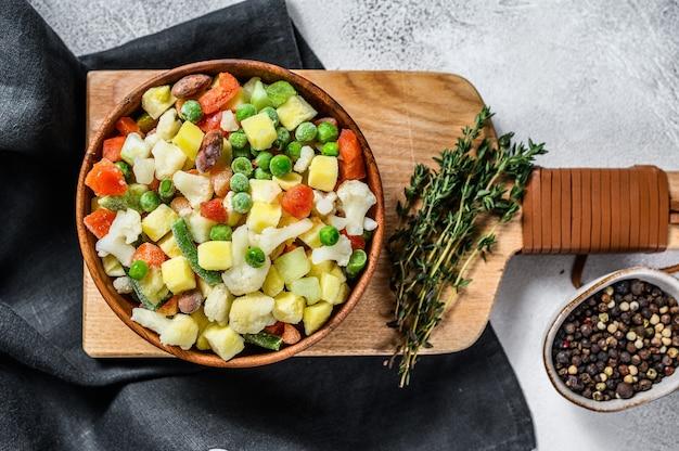Mrożone warzywa. brokuły, pomidorki koktajlowe, kukurydza, groszek, marchewka. białe tło. widok z góry.