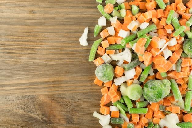 Mrożone warzywa mieszane na drewnianym stole. surowa siekana marchewka, kalafior, cebula, fasolka szparagowa i brukselka