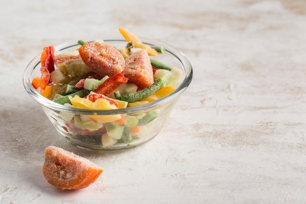 Mrożone warzywa. mieszanka warzyw, fasoli szparagowej i kalafiora w szklanej misce na jasnym tle.
