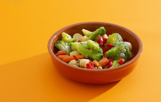 Mrożone warzywa na ceramicznym naczyniu do pieczenia: papryka, marchew, brokuły, kukurydza, pomidor i groszek na pomarańczowym tle.