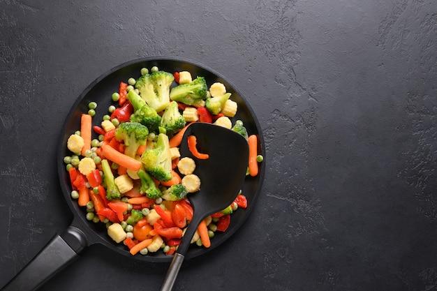Mrożone warzywa na patelni na czarnym tle widok z góry