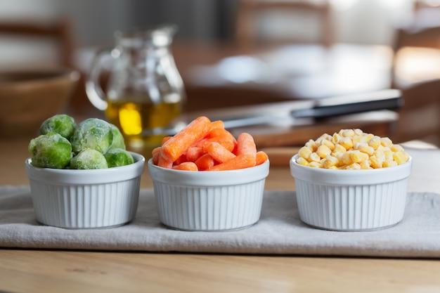 Mrożone warzywa, takie jak młoda marchewka i brukselka, w miskach na kuchennym stole, poziomo