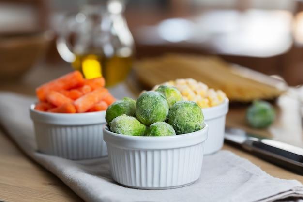 Mrożone warzywa, takie jak młoda marchewka i brukselka, w miskach na stole w kuchni