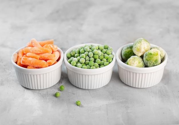 Mrożone warzywa, takie jak zielony groszek, brukselka i mała marchewka w białych miseczkach na betonowej szarej przestrzeni