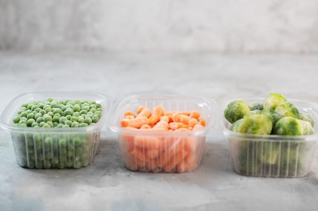 Mrożone warzywa, takie jak zielony groszek, brukselka i młoda marchewka w pudełkach do przechowywania na betonowej szarej przestrzeni