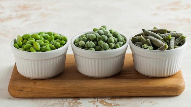 Mrożone warzywa, takie jak zielony groszek, soja, fasolka szparagowa i baby w białych miseczkach