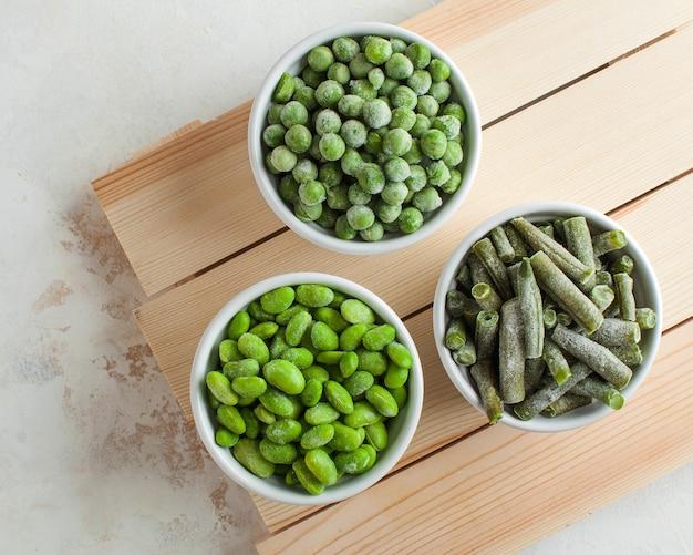 Mrożone warzywa zielony groszek, soja, fasolka szparagowa i żywność dla niemowląt w białych miseczkach