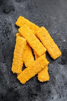 Mrożony chleb pokruszone paluszki rybne na stole czarny.