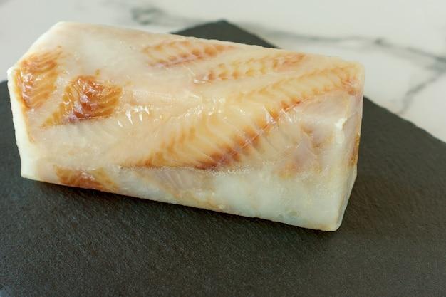Mrożony filet z ryby pangasius na kamiennej płycie gotowy do gotowania.