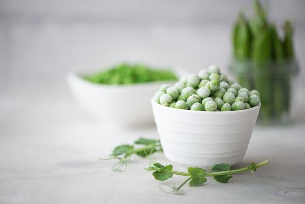 Mrożony i świeży zielony groszek w białej misce