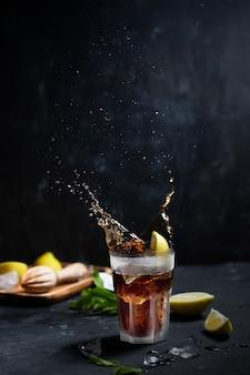 Mrożony koktajl cuba libre lub long island z mocnymi napojami, colą, cytryną i lodem
