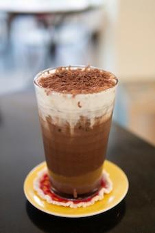 Mrożony napój czekoladowy z kakao z pianką śmietanową polany kakao w proszku zimny napój w kawiarni orzeźwiający