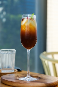 Mrożony sok owocowy mix z czarną kawą cold brew w kieliszku do wina na drewnianym stole w kawiarni.