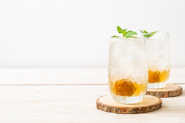Mrożony sok śliwkowy z sodą i miętą na drewnianym stole - napój orzeźwiający