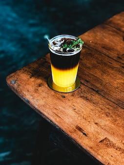 Mrożony świeży sok pomarańczowy zwieńczony espresso na drewnianym stole w nowoczesnej kawiarni.