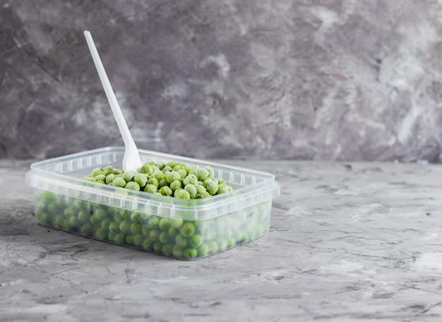 Mrożony zielony groszek w przezroczystym plastikowym pojemniku z widelcem na jasnej powierzchni
