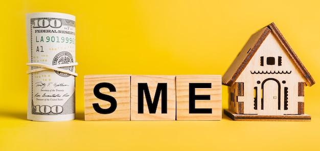 Mśp z miniaturowym modelem domu i pieniędzmi na żółtym tle. inwestycje, nieruchomości, dom, mieszkanie, zarobki, koncepcja finansowa