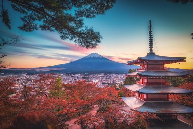 Mt. fuji z pagodą chureito i czerwonym liściem jesienią na zachodzie słońca w fujiyoshida, japonia.