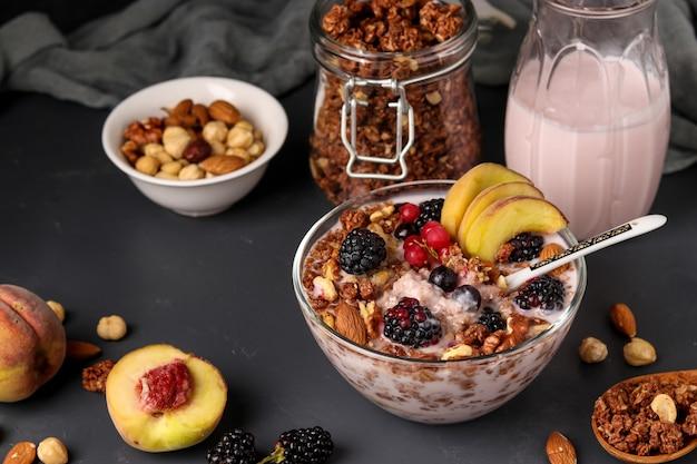 Muesli chrupiące musli miodowe granola z jogurtem naturalnym, świeżymi jagodami i owocami, czekoladą i orzechami w szklanej misce