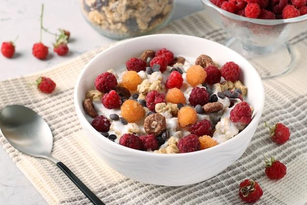 Muesli chrupiące musli z miodem i jogurtem naturalnym, świeżymi malinami czerwonymi i żółtymi