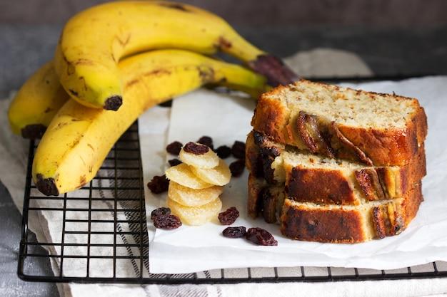 Muffin bananowy z kandyzowanym imbirem, rodzynkami i bananami na szarym tle.