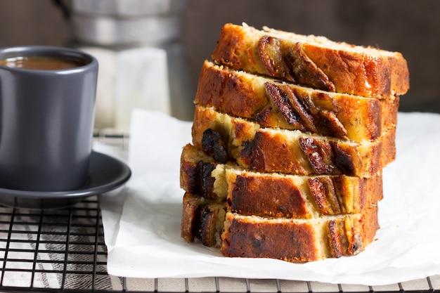 Muffin bananowy z kandyzowanym imbirem, rodzynkami i napojami na szarym tle.